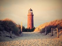 Historical lighthouse. Shinning lighthouse,  dunes and pine tree. Tower illuminated. With strong warning light, dark sky in background. Lighthouse tower built Royalty Free Stock Images
