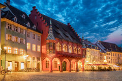 Historical Merchants Hall at dusk in Freiburg. Historical building of Merchants Hall Historisches Kaufhaus built in 1520-21 and located on Munsterplatz squre in Royalty Free Stock Images