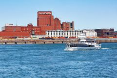 Historical Molson brewery building and a tour boat on saint Lawrence river in Montreal, Quebec, Canada. Montreal, Canada - June, 2018: Historical Molson brewery stock image