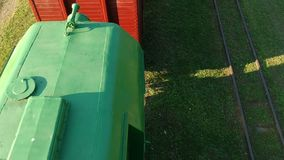 Historical narrow-gauge train in abandoned rail station, aerial