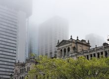 Historical Old Treasury Building viewed in early morning from the Victoria Bridge seen against the foggy highrise buidings of. The historical Old Treasury Royalty Free Stock Photos