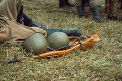 Historical reconstruction second world war. Helmet and rifle. Stock Photos