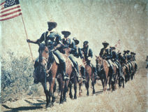 Historical reenactment of U.S. cavalry on horseback with American flag Stock Photos