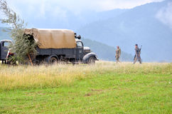 Historical reenactment of World War 2 battle - armored transport vehicle  and soldiers dressed in german nazi uniforms Royalty Free Stock Photography