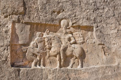 Historical relief carved between 239 - 70 AD about triumph of king Shapur I the Great. IRAN: Historical relief carved between 239 - 70 AD about triumph of king Stock Photos