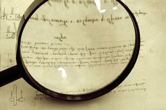 Historical Research. ~ magnifying glass over page of Leonardo Da Vinci's mirror-writing and technical drawings royalty free stock photo