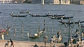 San Marco port. Historical restored footage of San Marco square and port in Venice with San Marco Basilica and typical gondolas boats, sea view. Tourists in stock footage