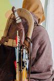 Historical set of old wooden arrows with bright plumage in the quiver on human back in the cloak  a hood Royalty Free Stock Images
