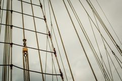 Historical sailship ropes ready for expedition. Historical ship sail ropes. Abstract rope lines and rope ladder. Dark sky with heavy clouds background Royalty Free Stock Photos