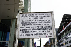 Historical sign at former East West Berlin border. Former Checkpoint Charlie, old sign with warning of leaving the american sector. After Second World War and Stock Photos