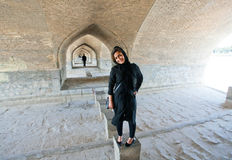 Historical stone Khaju Bridge and cute young persian woman. ISFAHAN, IRAN: Historical stone Khaju Bridge and cute young persian woman stands under. Best example Royalty Free Stock Images