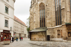 Historical street with brick walls of cathedral and some walking people. VIENNA, AUSTRIA - JUN 10: Historical street with brick walls of cathedral and some royalty free stock photos