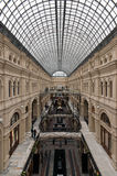 Historical symmetrical interior with glass ceiling. Rich decorated interior of historical building of classical architecture with steel framework  and glass roof Stock Photos