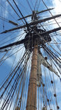 Historical tall mast on sailing ship vertical. Tall mast on vintage sailing ship preparing to sail against a bright blue  sky Royalty Free Stock Image