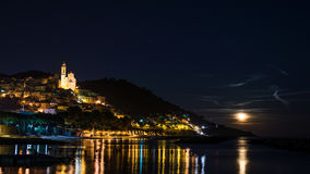 The historical town of Cervo glowing in the night under moonlight and starry sky on the coastline of Ligurian Riviera, famous trav Stock Images
