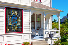 Historical white American house porch with stain glass window. Royalty Free Stock Photo