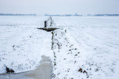 Historical windmills in a cold and snowy Dutch farmland. stock photo