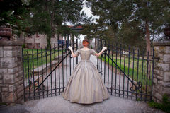 Historical Woman Enters Gate to Mansion Royalty Free Stock Photos
