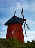 Historical wooden windmill. A historical, typical red - colored wooden windmill. Blue sky on the background and bushes on foreground Stock Images