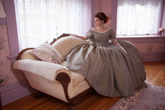 Historically Clad Woman Sitting on Couch and Looking out Window Royalty Free Stock Photo