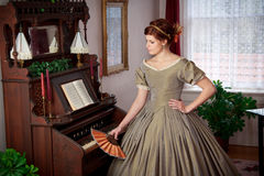 Historically Clad Woman Standing by a Pump Organ Royalty Free Stock Image