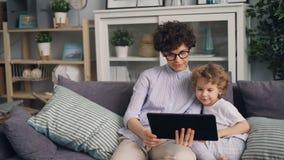 Historietas de observación del muchacho adorable en la tableta con su artilugio de la tenencia de la madre que cuida metrajes