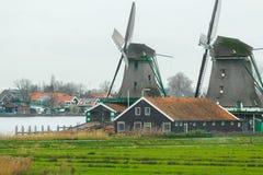 Historisch Nederlands dorp met oud windmolens en rivierlandschap Stock Afbeelding
