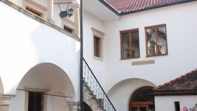 Historische binnenplaats Historisch huis met mooie bloemen en historische waterput stock videobeelden