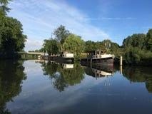 Historische Boote und ihre Reflexion in einem Fluss Lizenzfreie Stockfotos