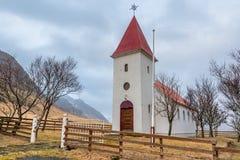 Historische die Kalfafellsstadur-Kerk in IJsland door bomen en een berg wordt omringd royalty-vrije stock afbeelding