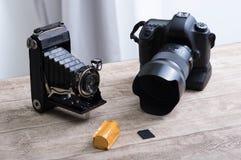 Historische Kamera mit Bälgen und gegenwärtiges digitales SLR mit Film Stockbild