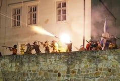 Historische Kampfrekonstruktion - Musketiere auf einem Wallschießen nachts lizenzfreies stockbild