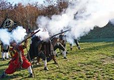 Historische Kampfrekonstruktion - Musketiere in Folge, die auf einem grünen Feld schießen lizenzfreies stockfoto