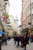 Historische Mittelstraße mit Leuten, Shopschildern und alter Architektur Stockfotos