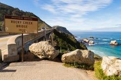Historische Rocky Creek Bixby Creek-Brücke mit Zeichen und Ansicht von Ozean von der Pazifikküstelandstraße in Kalifornien lizenzfreie stockfotografie