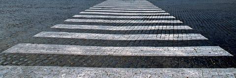 Historische Steinstraße mit Zebraüberfahrt Stockfotos