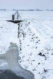 Historische Windmühlen in einem kalten und schneebedeckten niederländischen Ackerland Stockfotos