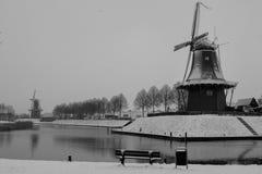 Historische Windmühlen im Schnee nahe bei Wasser Stockbild