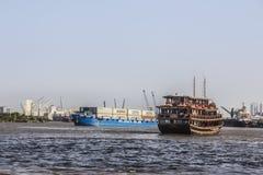 Historischer Lastkahn und ein Containerschiff stockfotos