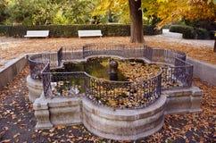 Historischer schöner Brunnen im alten Stadtpark mit Bank im Herbst Stockfotos