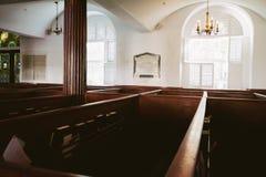 Historischer schauender Kirchengebäudeinnenraum mit Mann machte hölzerne Bänke und großes Glas-Windows stockbild
