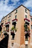 Historisches Gebäude mit acht Balkonen voll von Blumen in Venedig Stockfotografie