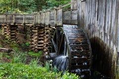 Historisches hölzernes gristmill mit Arbeitswasserrad stockfotos