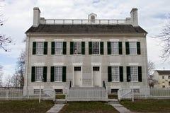 Historisches Haus des Schüttels-Apparat hinter einem weißen Palisadenzaun. Stockbild