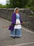 Historisches Mädchen in einem Kostüm mit einer Muskete auf den Wänden von Londonderry stockfotos