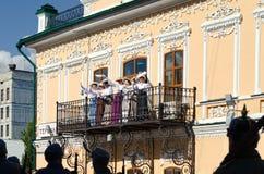 Historisk festivalShadrinsk stad, Ryssland Juni 25, 2017 Damer som vinkar näsdukar från balkongen, förbi botten, är arkivfoton