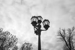 Historisk formsvartlyktstolpe med fyra lyktor framme av himmel- och molnbakgrund Nostalgisk gatalykta arkivbilder