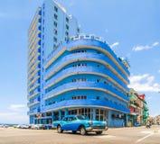 Historisk gammal blå byggnad bredvid stranden och en retro tappning slösar bilen framme i Kubahavannacigarr Arkivbild