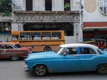 Historisk gammal blå byggnad bredvid stranden och en retro tappning slösar bilen framme i Kubahavannacigarr Arkivfoton