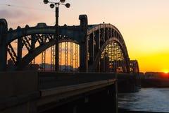 Historisk gammal bro i solnedgång, Bolsheokhtinsky bro Royaltyfri Bild
